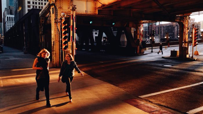 two-women-walk-on-well-street-sidewalk-at-sunset-102814